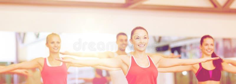 Grupo de gente sonriente que ejercita en el gimnasio foto de archivo libre de regalías