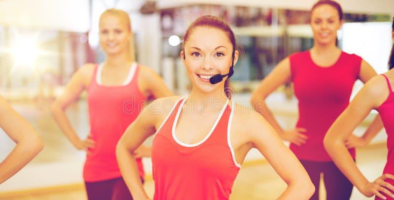 Grupo de gente sonriente que ejercita en el gimnasio foto de archivo