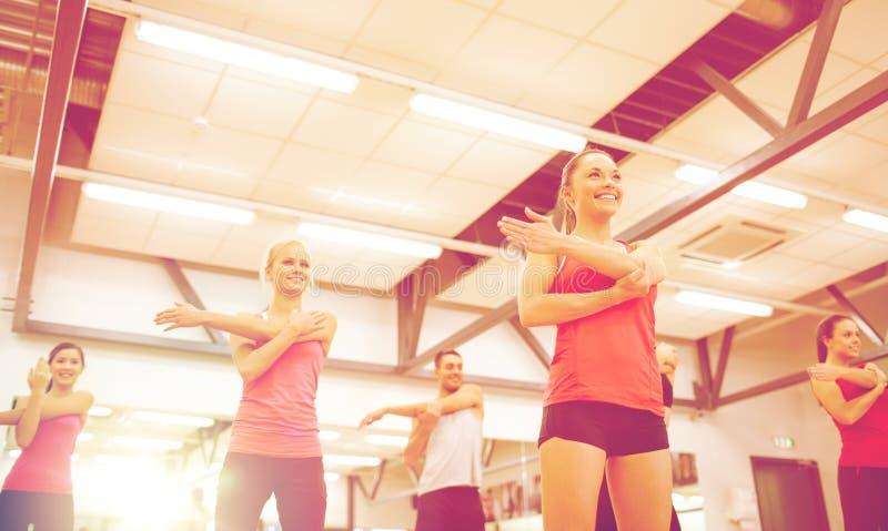 Grupo de gente sonriente que estira en el gimnasio foto de archivo