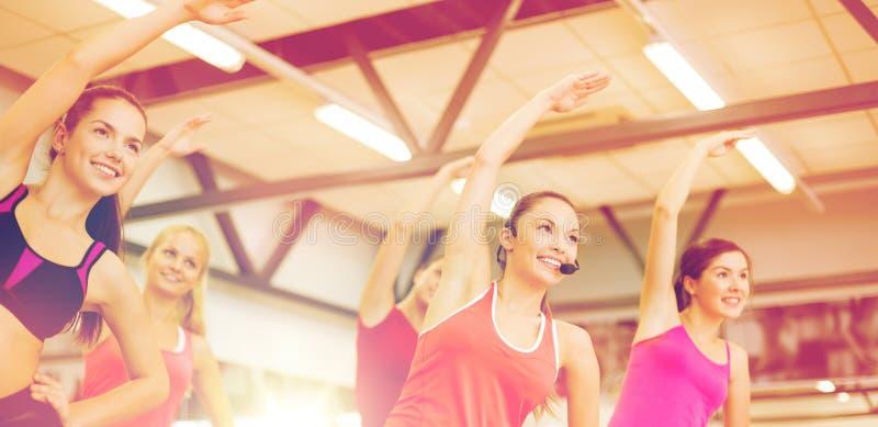 Grupo de gente sonriente que estira en el gimnasio fotografía de archivo libre de regalías