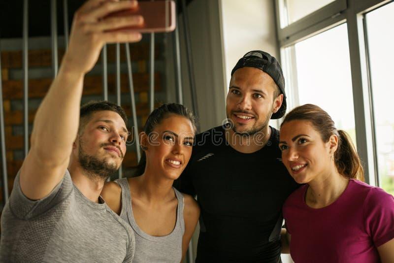 Grupo de gente sonriente que hace la uno mismo-imagen en gimnasio imagenes de archivo