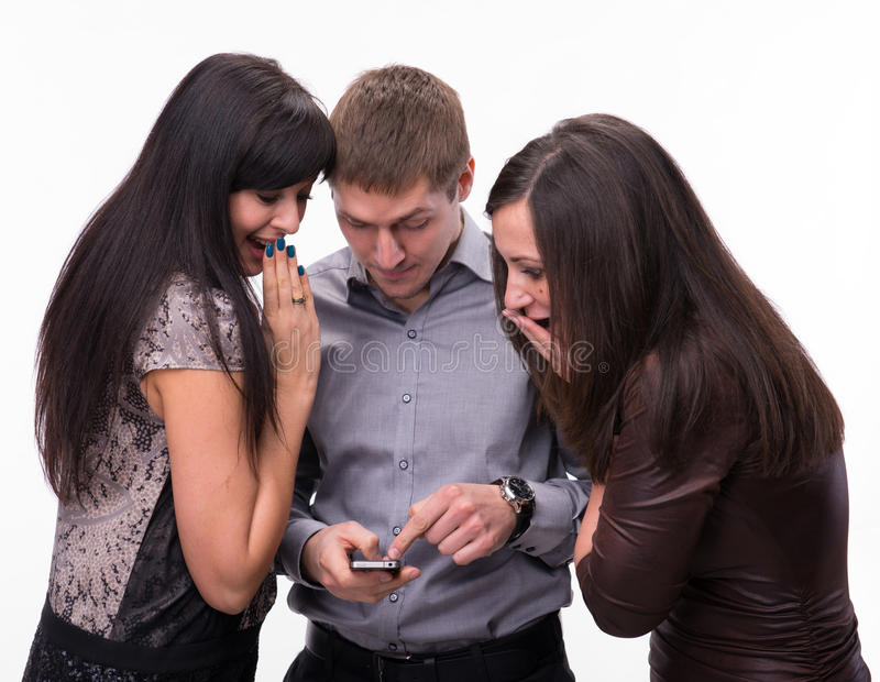 Grupo de gente sorprendida que mira un teléfono celular fotografía de archivo