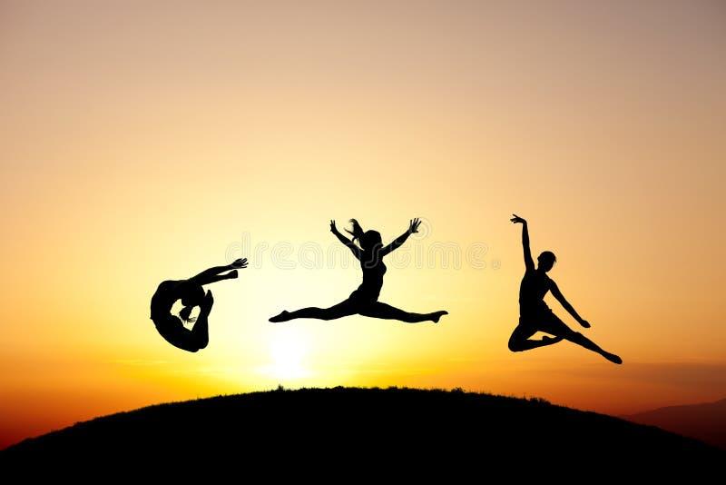 Grupo de ginastas que saltam no por do sol imagem de stock royalty free
