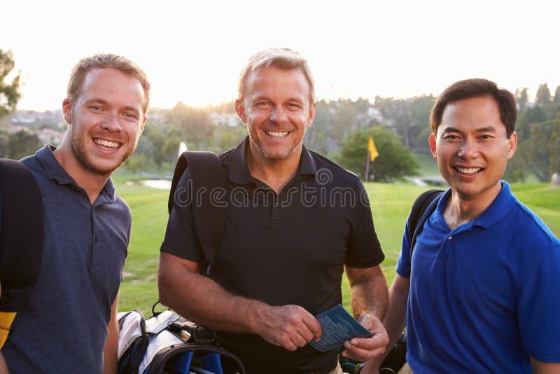Grupo de golfistas de sexo masculino que marcan la tarjeta de puntuación en el final de redondo foto de archivo