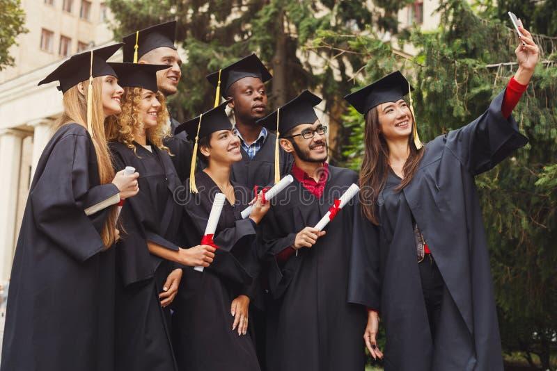 Grupo de graduados que celebran y que hacen el selfie foto de archivo