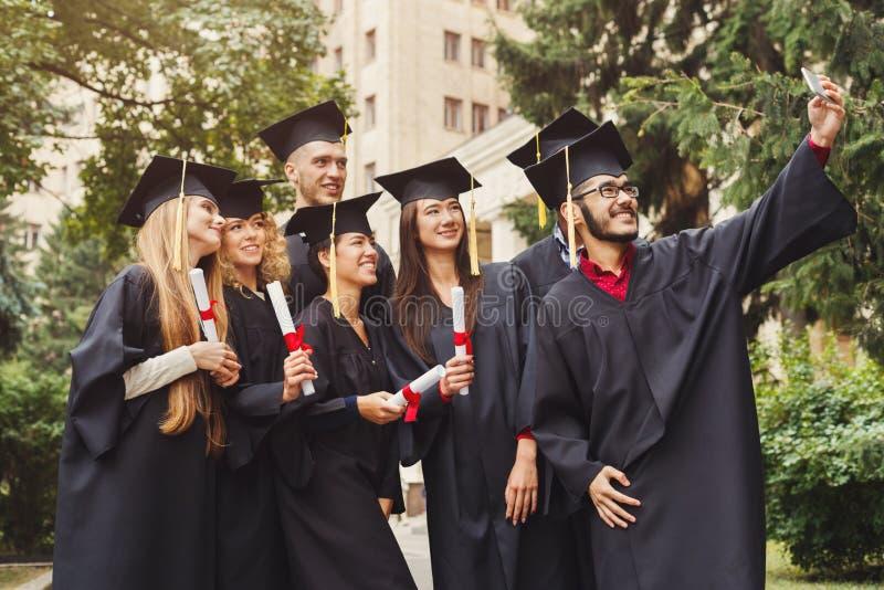 Grupo de graduados que comemoram e que fazem o selfie fotografia de stock