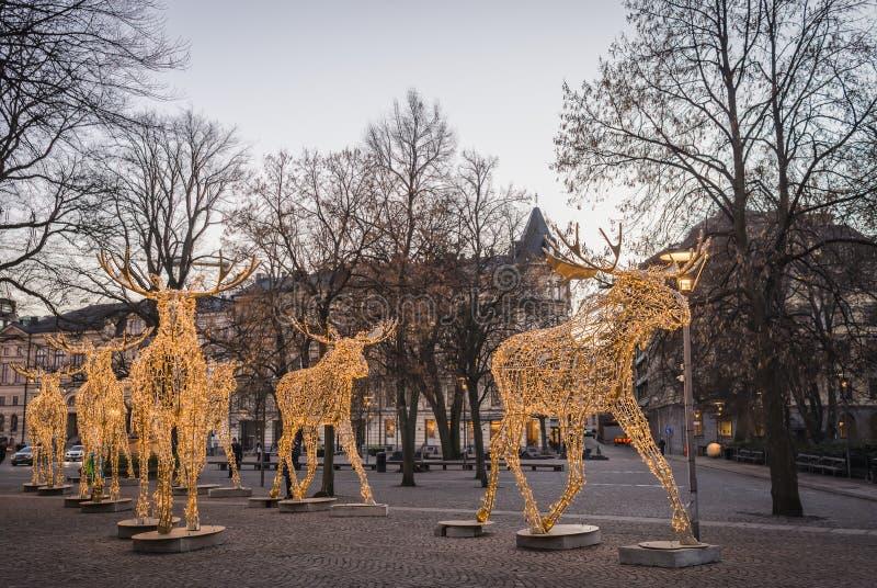 Grupo de grandes esculturas dos alces feitas de luzes conduzidas em Nybrokajen durante a estação do Natal foto de stock