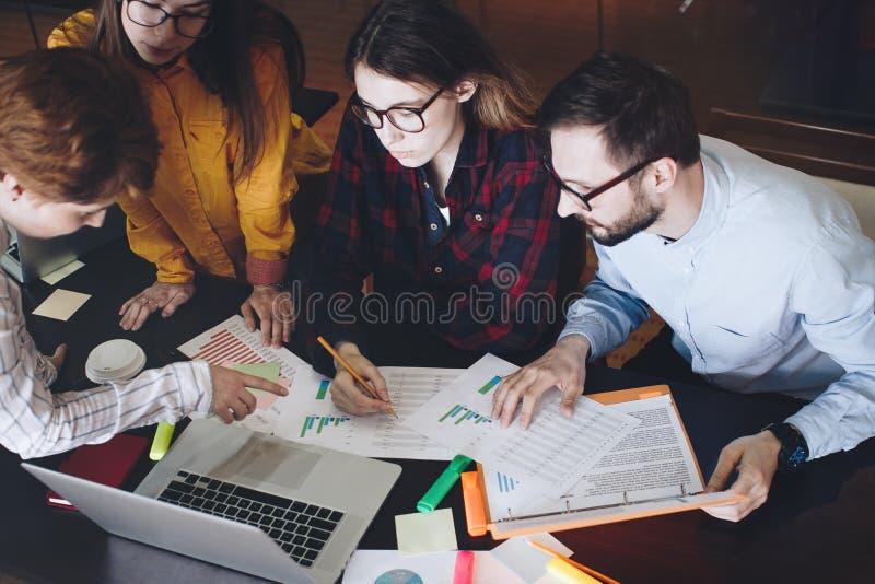 Grupo de hembra y de varón de los estudiantes que discuten diagramas y gráficos El equipo de ingenieros mira los resultados de lo fotos de archivo libres de regalías