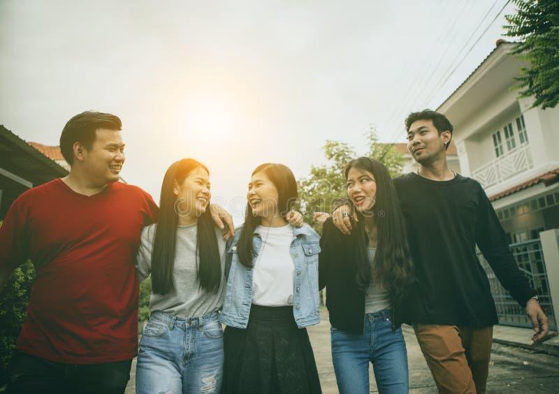 Grupo de hombre más joven asiático y de mujer que relajan el fac sonriente dentudo imagen de archivo