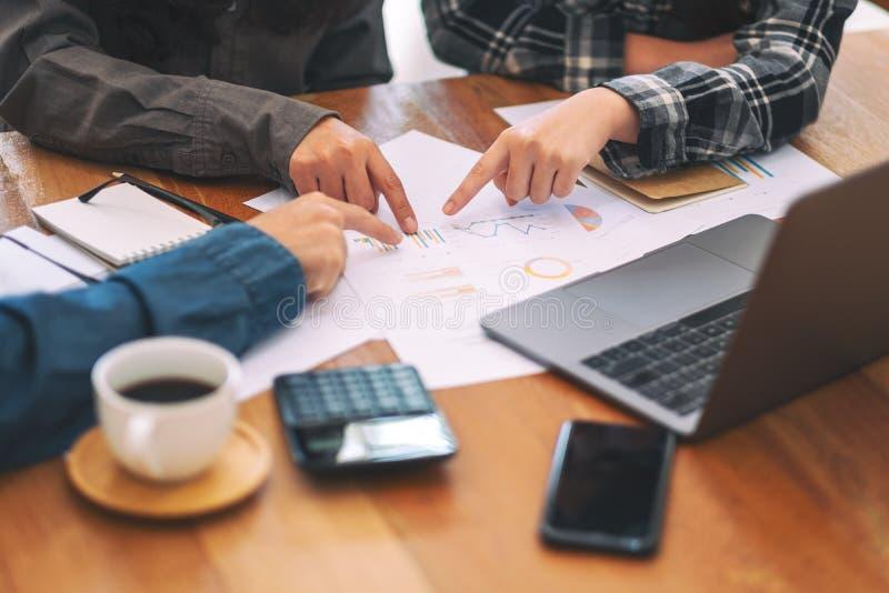 Grupo de hombre de negocios que señala los fingeres en el papeleo mientras que discute negocio junto foto de archivo