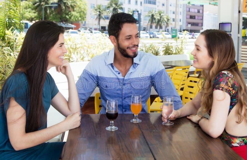 Grupo de hombre y de mujer que hablan en una barra fotografía de archivo