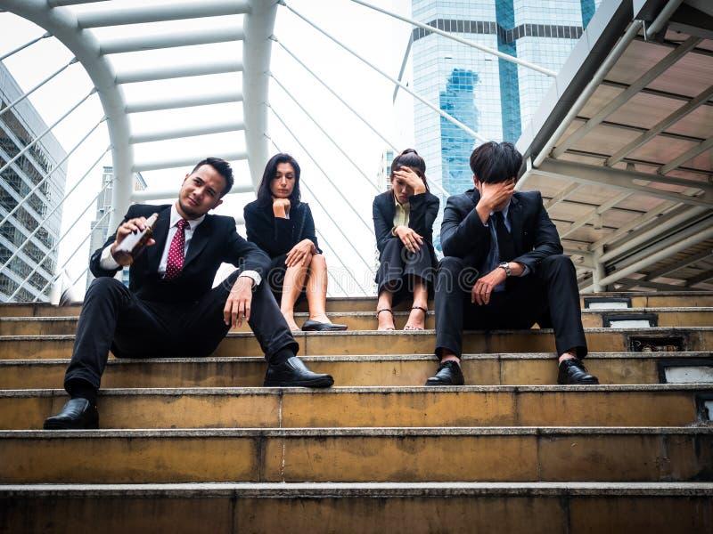 Grupo de hombre y de mujer de negocios que se sientan en parque del aire libre y subrayados debido a fracaso de negocio foto de archivo libre de regalías
