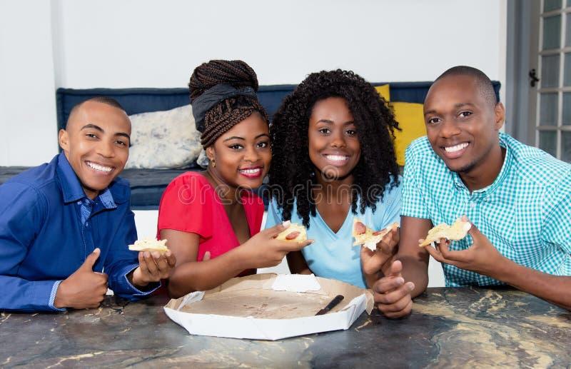 Grupo de hombres afroamericanos y de mujeres que comen la pizza foto de archivo libre de regalías