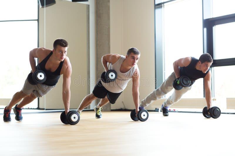 Grupo de hombres con pesas de gimnasia en gimnasio imagenes de archivo