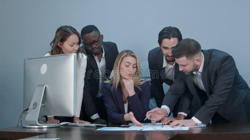 Grupo de hombres de negocios jovenes diversos multiétnicos en una reunión que se coloca alrededor de una tabla con expresiones se fotografía de archivo libre de regalías