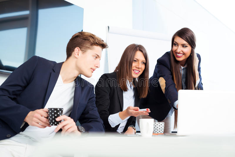 Grupo de hombres de negocios jovenes felices en una reunión en la oficina imagenes de archivo