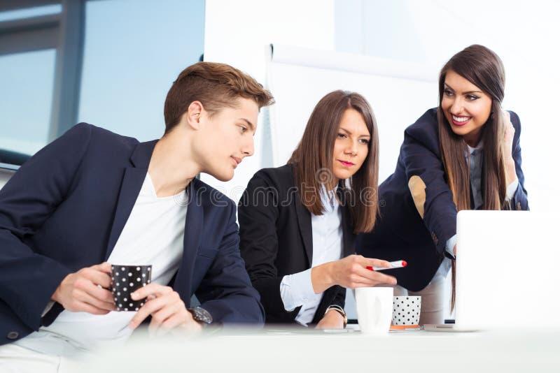 Grupo de hombres de negocios jovenes felices en una reunión en la oficina foto de archivo libre de regalías