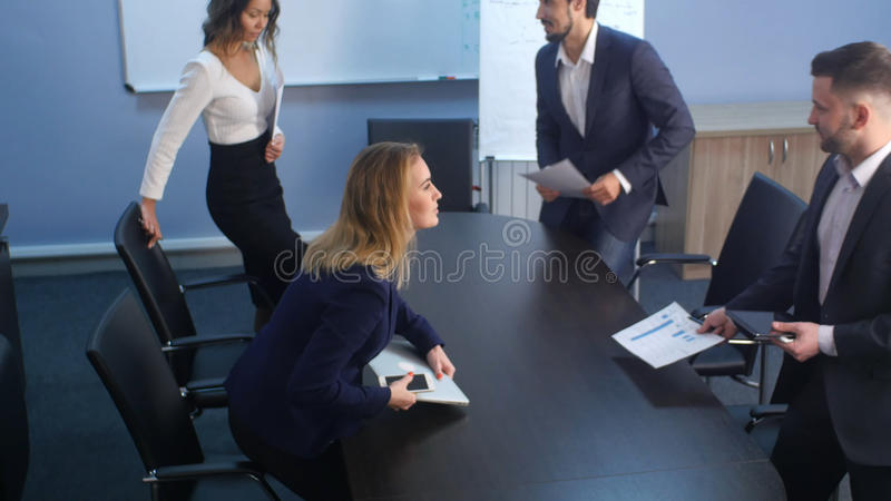 Grupo de hombres de negocios jovenes que vienen junto a la oficina imagenes de archivo