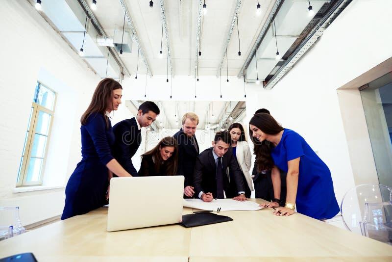 Grupo de hombres de negocios prósperos jovenes en la ropa corporativa que trabaja junto en equipo en proyectos comunes, foto de archivo