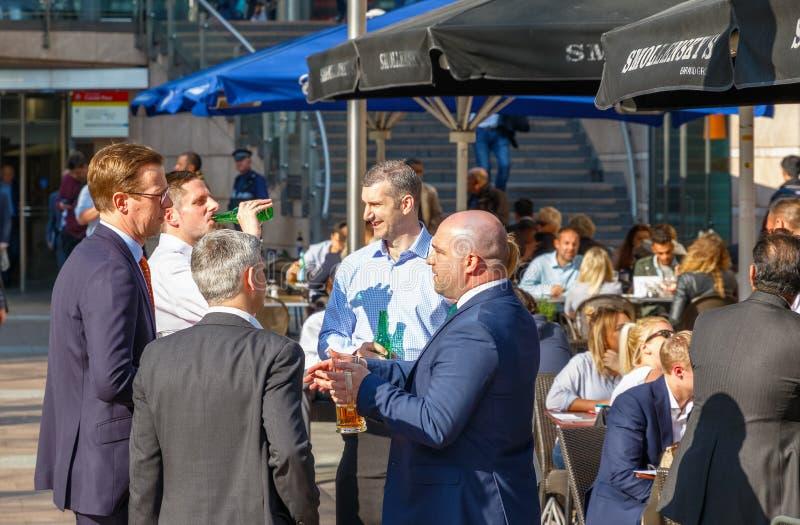 Grupo de hombres de negocios que beben en una barra al aire libre en Canary Wharf imagen de archivo libre de regalías