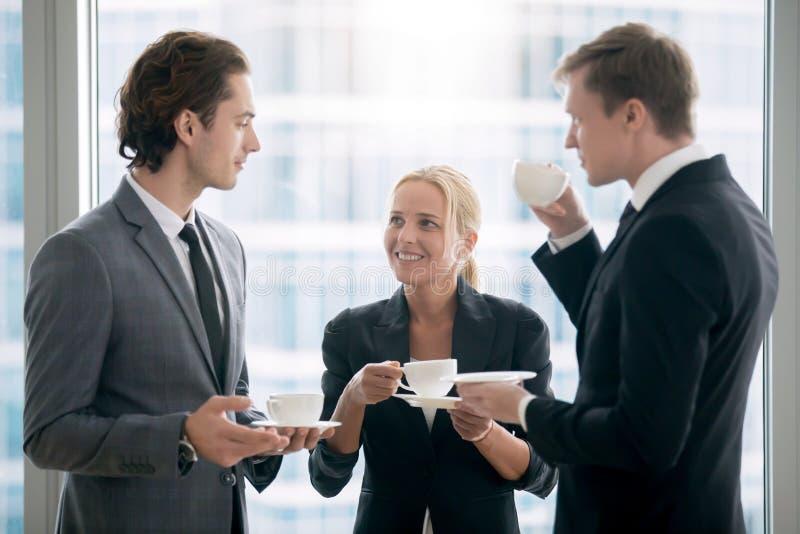 Grupo de hombres de negocios que comen té después de encontrar imágenes de archivo libres de regalías