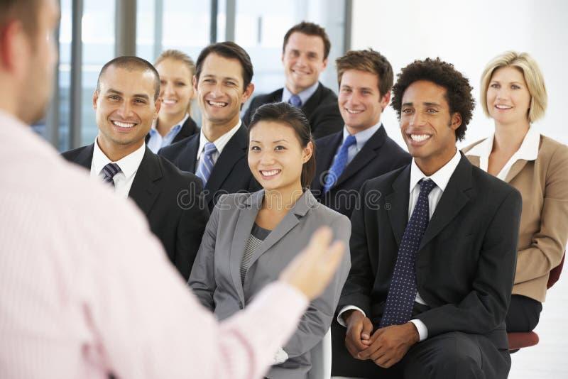 Grupo de hombres de negocios que escuchan el Presidente que da la presentación imágenes de archivo libres de regalías