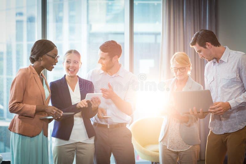 Grupo de hombres de negocios que obran recíprocamente usando el teléfono móvil, la tableta digital y el ordenador portátil foto de archivo libre de regalías