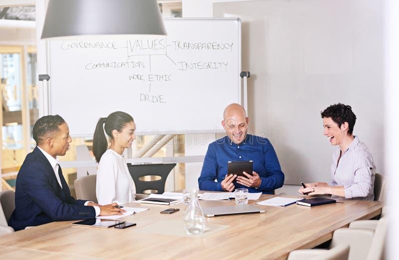 Grupo de hombres de negocios que ríen junto en una sala de conferencias imagenes de archivo