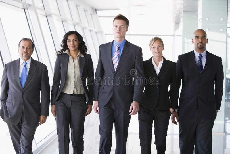 Grupo de hombres de negocios que recorren hacia cámara imagen de archivo
