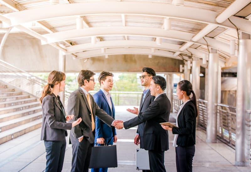 Grupo de hombres de negocios que sacuden las manos, trabajo en equipo acabando para arriba meetingpartners saludándose después de imagen de archivo