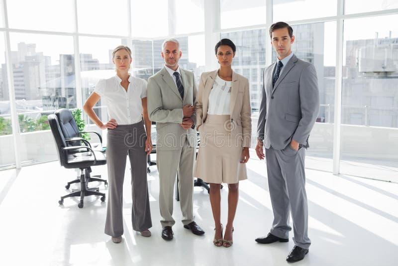 Grupo de hombres de negocios que se colocan en línea fotos de archivo