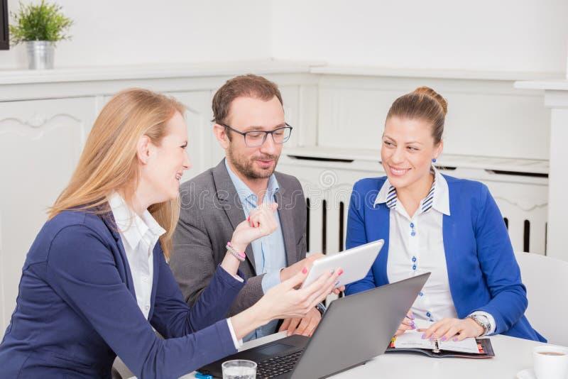 Grupo de hombres de negocios que se encuentran alrededor de la mesa de reuniones foto de archivo libre de regalías