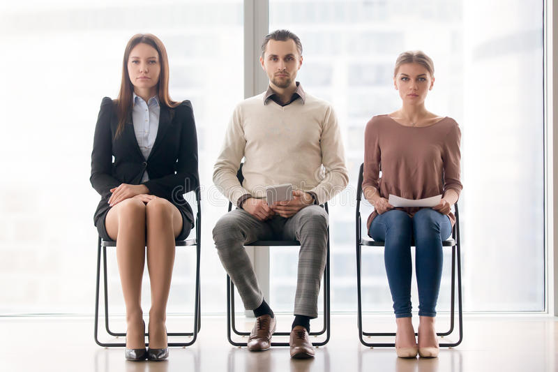 Grupo de hombres de negocios que se sientan en las sillas que miran la cámara fotos de archivo