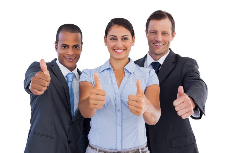 Grupo de hombres de negocios sonrientes que muestran sus pulgares para arriba imágenes de archivo libres de regalías