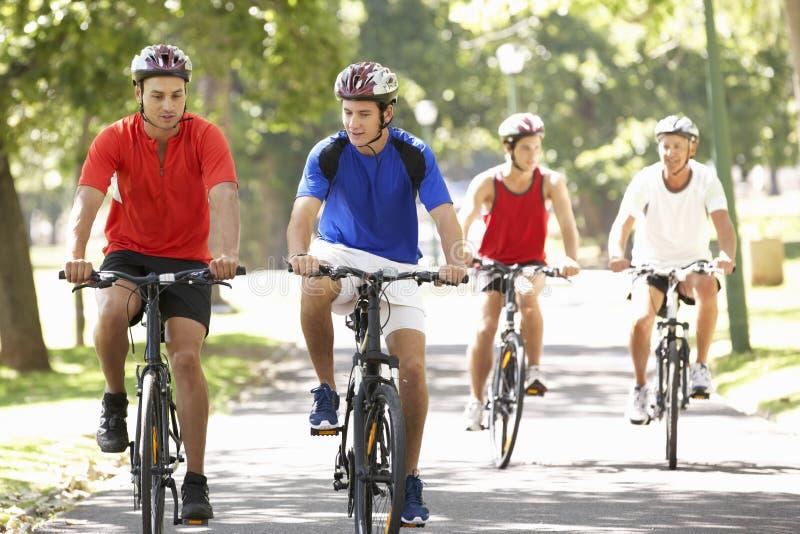 Grupo de hombres en paseo del ciclo a través del parque imágenes de archivo libres de regalías