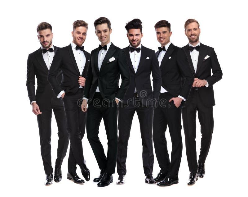 Grupo de hombres jovenes elegantes en los smokinges que se unen imagen de archivo