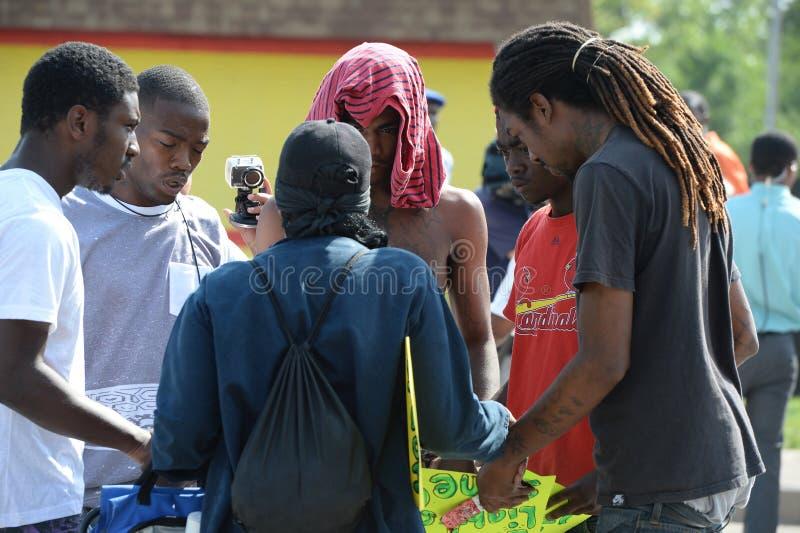 Grupo de hombres jovenes que ruegan en Ferguson imagen de archivo