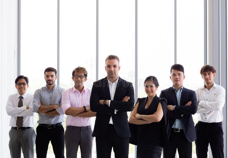 Grupo de hombres de negocios con los brazos cruzados en oficina imagenes de archivo