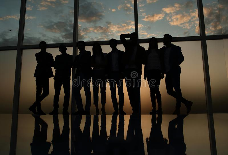 Grupo de hombres de negocios jovenes felices que se colocan cerca de una ventana grande de la oficina imagen de archivo