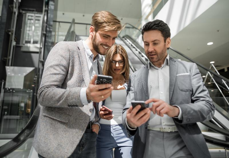 Grupo de hombres de negocios jovenes que miran las pantallas de sus smartphones imágenes de archivo libres de regalías