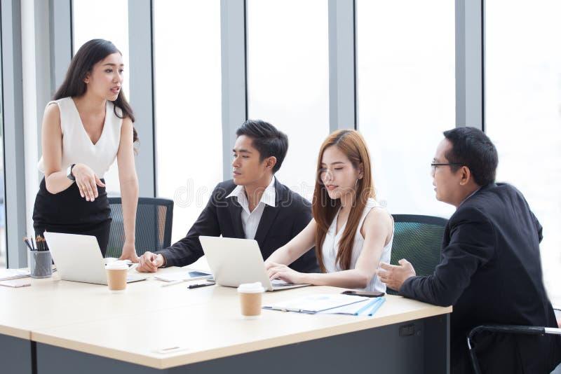 Grupo de hombres de negocios jovenes que se inspiran junto en la sala de reunión Empresaria que presenta a los colegas Trabajo en imagenes de archivo