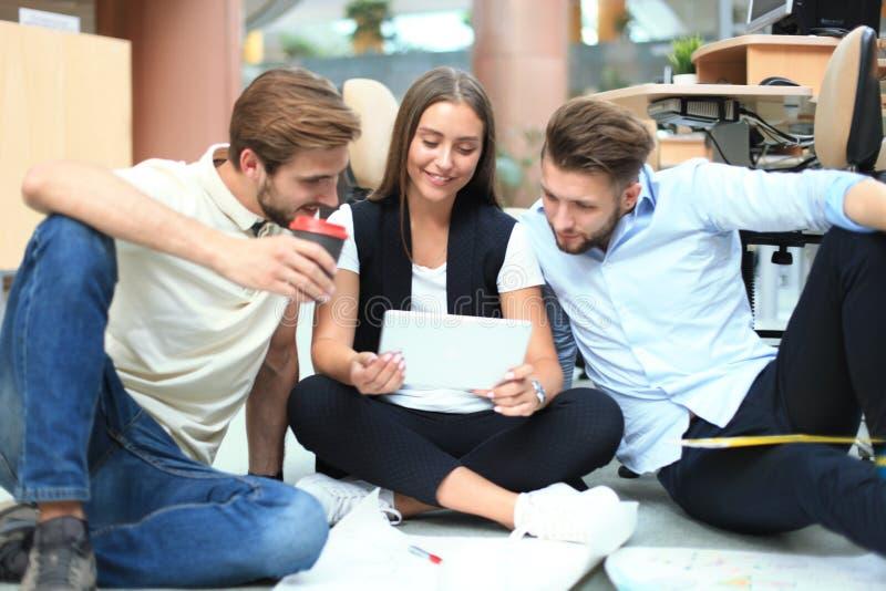 Grupo de hombres de negocios jovenes y de diseñadores que miran el plan del proyecto presentado en piso Ellos que trabajan en nue fotos de archivo
