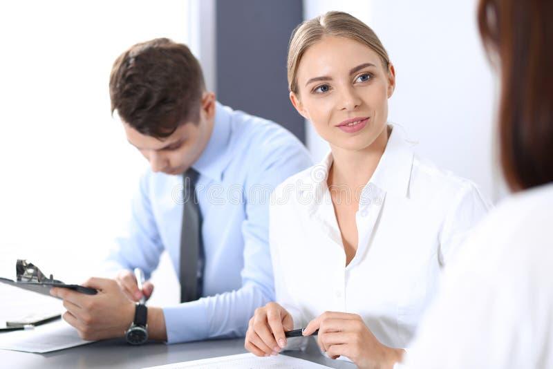 Grupo de hombres de negocios o de abogados que discuten términos de la transacción en oficina Concepto de la reunión y del trabaj imagen de archivo