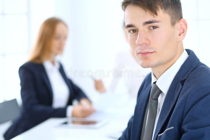 Grupo de hombres de negocios o de abogados que discuten términos de la transacción en oficina Foco en el hombre de negocios joven fotografía de archivo libre de regalías