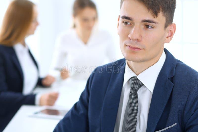 Grupo de hombres de negocios o de abogados que discuten términos de la transacción en oficina Foco en el hombre de negocios joven imagen de archivo