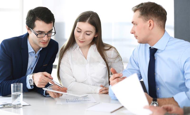 Grupo de hombres de negocios que discuten preguntas en el encuentro en oficina moderna Encargados en la negociaci?n o el intercam imagen de archivo libre de regalías