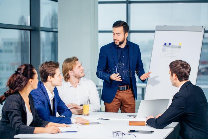 Grupo de hombres de negocios que miran el gráfico en flipchart foto de archivo