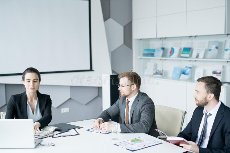 Grupo de hombres de negocios que se encuentran en la sala de conferencias imagen de archivo libre de regalías
