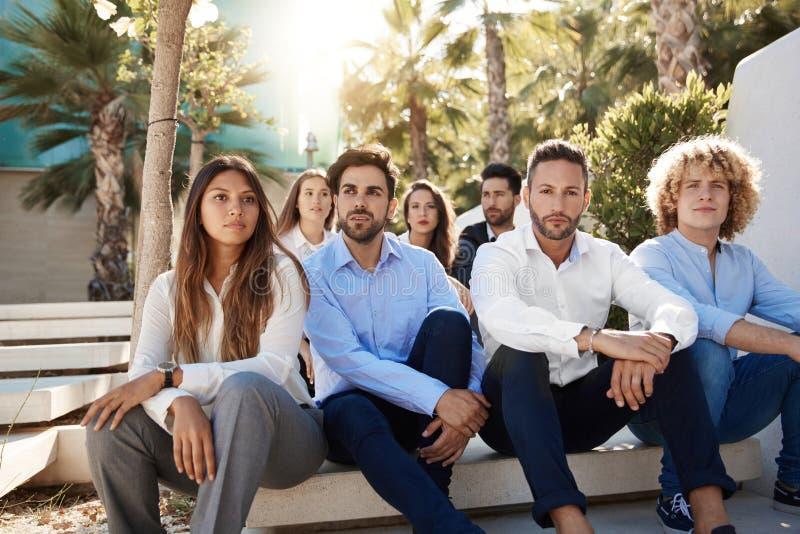 Grupo de hombres de negocios que se sientan afuera fotos de archivo libres de regalías