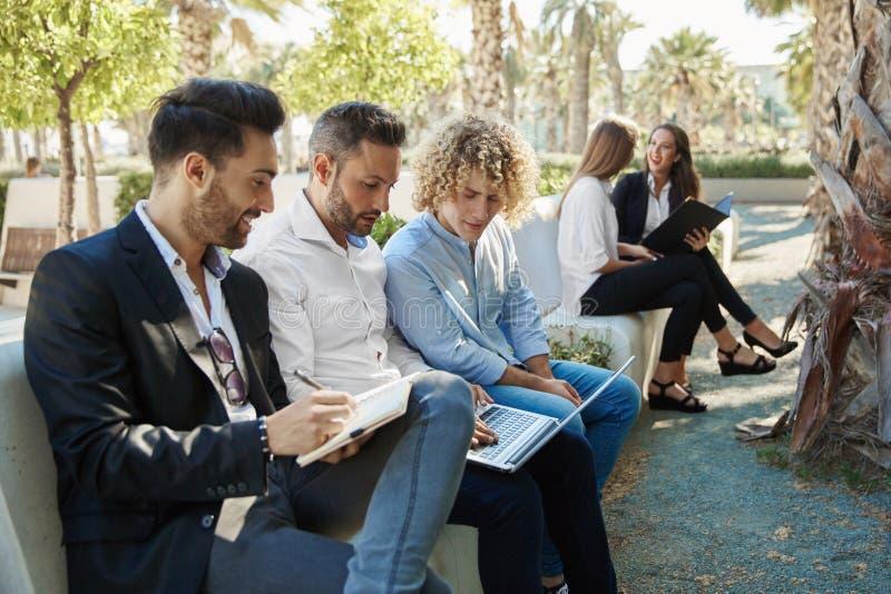 Grupo de hombres de negocios que trabajan afuera junto imagen de archivo